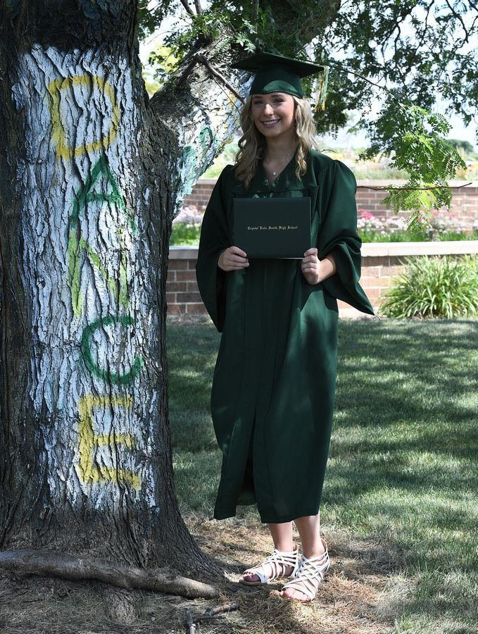 Crystal Lake South High School graduate Madison Kroening, 18, of Lake in the Hills stands next to the dance sign she painted on a tree after she received her diploma in a red carpet celebration on Friday at the school.