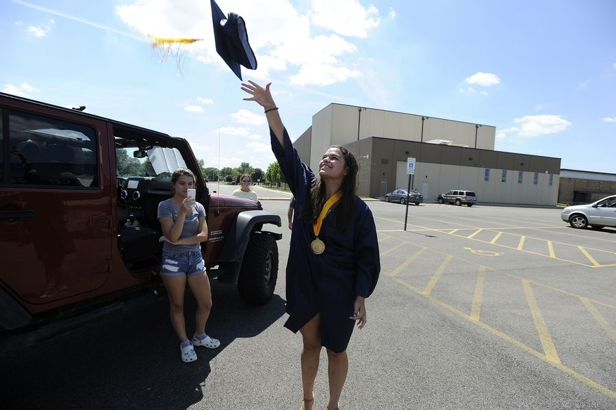 Cary-Grove High School graduate Lydia Forney, 18, of Cary enjoys the moment by tossing her cap into the air after she received her diploma Friday.