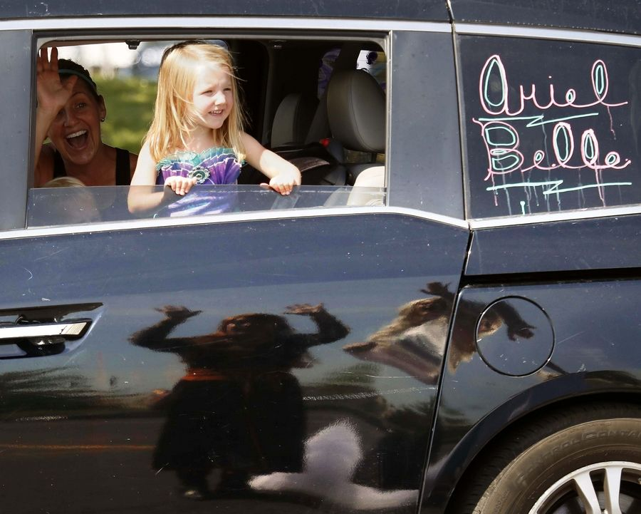 Erin Tosch of Arlington Heights and her daughters, Alice, 4, right, and Julie, 2, wave to princesses (reflected on car) during a character parade Saturday in the Sears Centre Arena parking lot in Hoffman Estates.