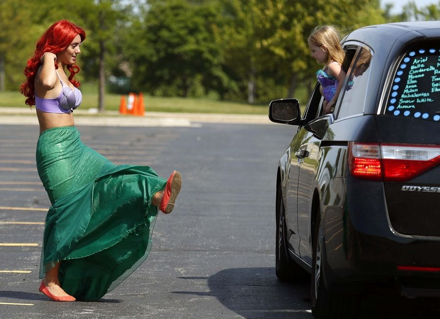 Princess Ariel shows four-year-old Alice Tosch of Arlington Heights her shoes during a character parade Saturday in the Sears Centre Arena parking lot in Hoffman Estates. Ariel is portrayed by Grace Biernacki of Party Princesses.