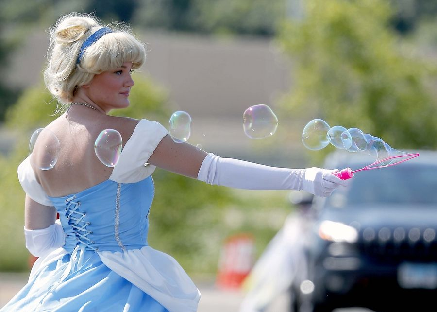 Kayla Gustafson, who is dressed as Cinderella, waves her bubble wand during a character parade Saturday in the Sears Centre Arena parking lot in Hoffman Estates.