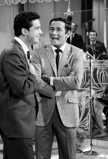 "FILE - In this Sept. 15, 1967 file photo, Regis Philbin, of ""The Joey Bishop Show"" goes over the upcoming routines with Joey Bishop, right, on the set of the ABC-TV studio inLos Angeles. Philbin, the genial host who shared his life with television viewers over morning coffee for decades and helped himself and some fans strike it rich with the game show 'œWho Wants to Be a Millionaire,'� has died on Friday, July 24, 2020."