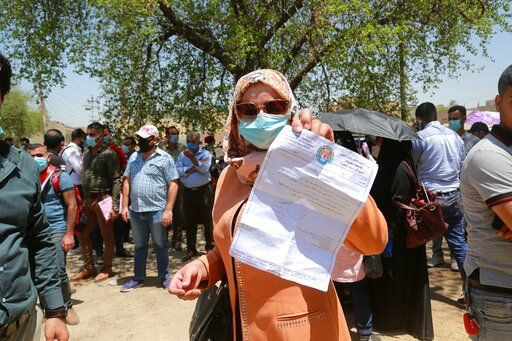 Rowaida Abdul Rahman shows her science master's degree certificate while jobless graduates gather in front of the Ministry of Oil to demand jobs in Baghdad, Iraq, Monday, July 20, 2020. In the Mideast, wave after wave of war, disease and economic collapse leaves this generation feeling hopeless.