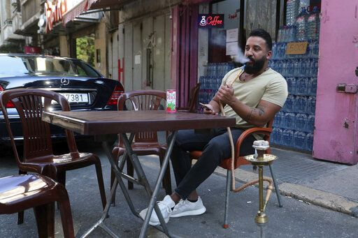 Lebanese Wissam al-Sheikh, 30, who recently lost his job as manager at a clothes store in downtown Beirut, smokes a water-pipe at a coffee shop in Beirut, Lebanon, Wednesday, July 22, 2020. Millions of youth in the Middle East region have had job prospects, plans for higher education and marriage upended by the pandemic. While such turmoil and uncertainty is universal in the wake of the coronavirus, the despair is particularly pronounced in Arab countries, where wave after wave of war, displacement and corruption has left this generation feeling bitter and hopeless.