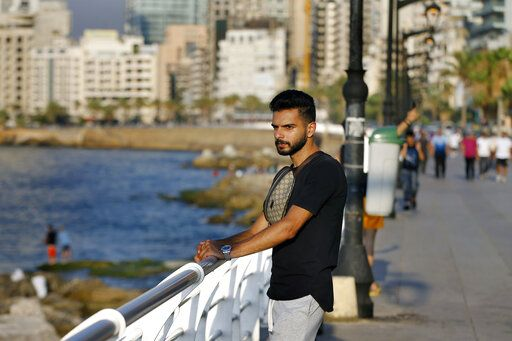Lebanese Ali Mallah, 27, who recently lost his job as a salesman at a shoe store in Beirut, stands on Beirut's waterfront promenade on the Mediterranean Sea in Beirut, Lebanon, Wednesday, July 22, 2020. Millions of youth in the Middle East region have had job prospects, plans for higher education and marriage upended by the pandemic. While such turmoil and uncertainty is universal in the wake of the coronavirus, the despair is particularly pronounced in Arab countries, where wave after wave of war, displacement and corruption has left this generation feeling bitter and hopeless.