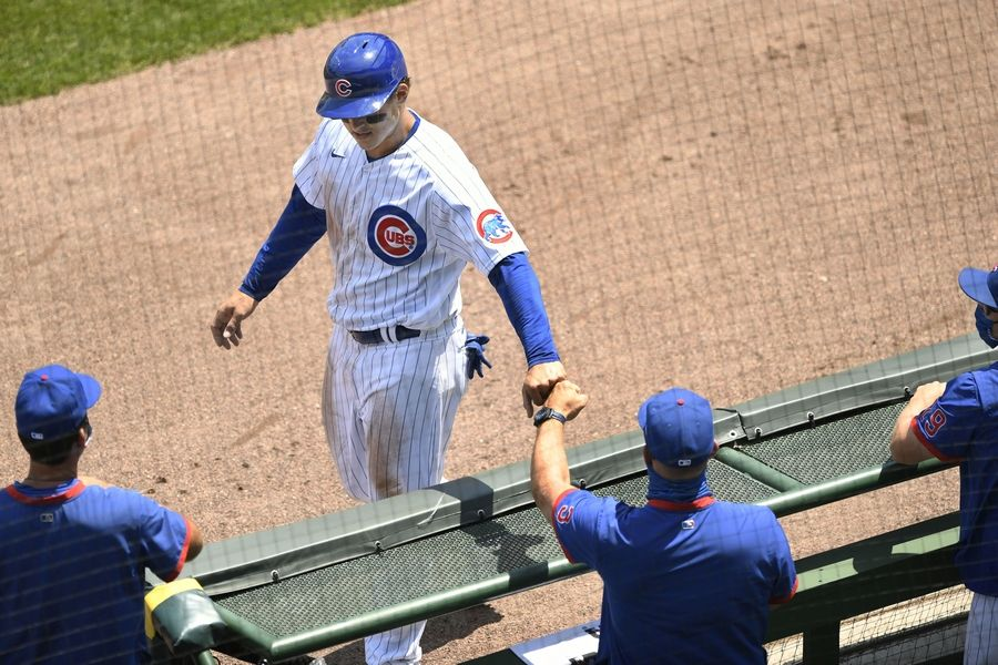 Chicago Cubs' Anthony Rizzo celebrates with manager David Ross after scoring on a single hit by Willson Contreras during the first inning of a baseball game against the Milwaukee Brewers Saturday, July 25, 2020, in Chicago.