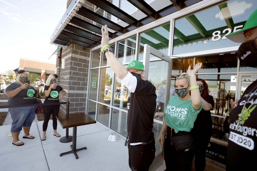 Donnie Wahlberg and Jenny McCarthy greet the crowd outside Wahlburgers restaurant opening day Tuesday in St. Charles.