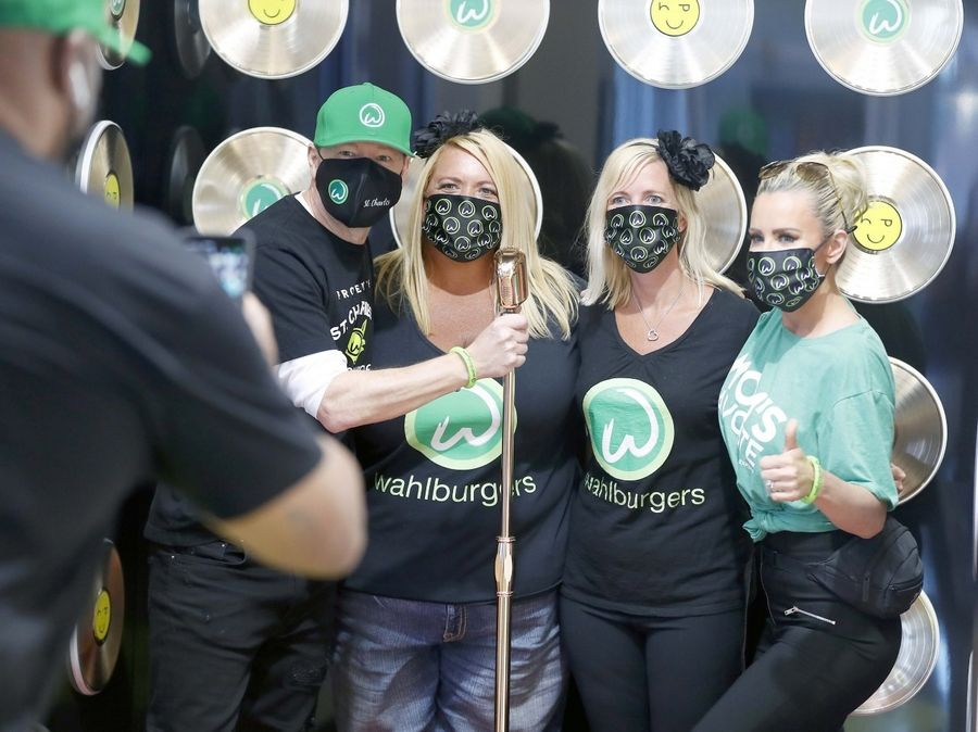 Chrissie Butkus, center right, and Michelle Greybill, center left, both of New Lenox get their picture taken with Donnie Wahlberg and Jenny McCarthy Wahlburgers restaurant opening day Tuesday in St. Charles. Butkus and Greybill arrived at 5:20 in the morning to make sure that they were first in line.