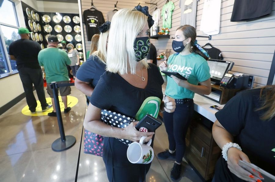 Chrissie Butkus of New Lenox makes her way into Wahlburgers restaurant on opening day Tuesday in St. Charles. Butkus arrived at 5:20 in the morning to make sure that they were first in line.
