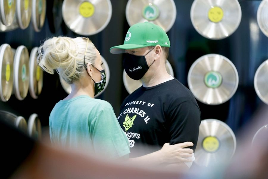 Donnie Wahlberg and Jenny McCarthy take a second before greeting guests at the new Wahlburgers restaurant on opening day in St. Charles.