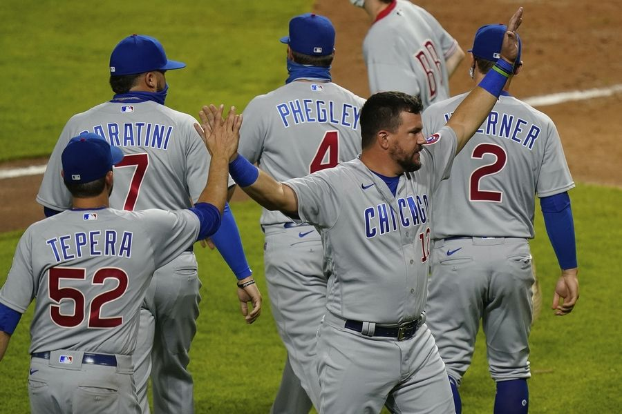 Chicago Cubs' Kyle Schwarber (12) celebrates with teammates after the Cubs defeated the Cincinnati Reds 8-7 in a baseball game in Cincinnati, Monday, July 27, 2020.