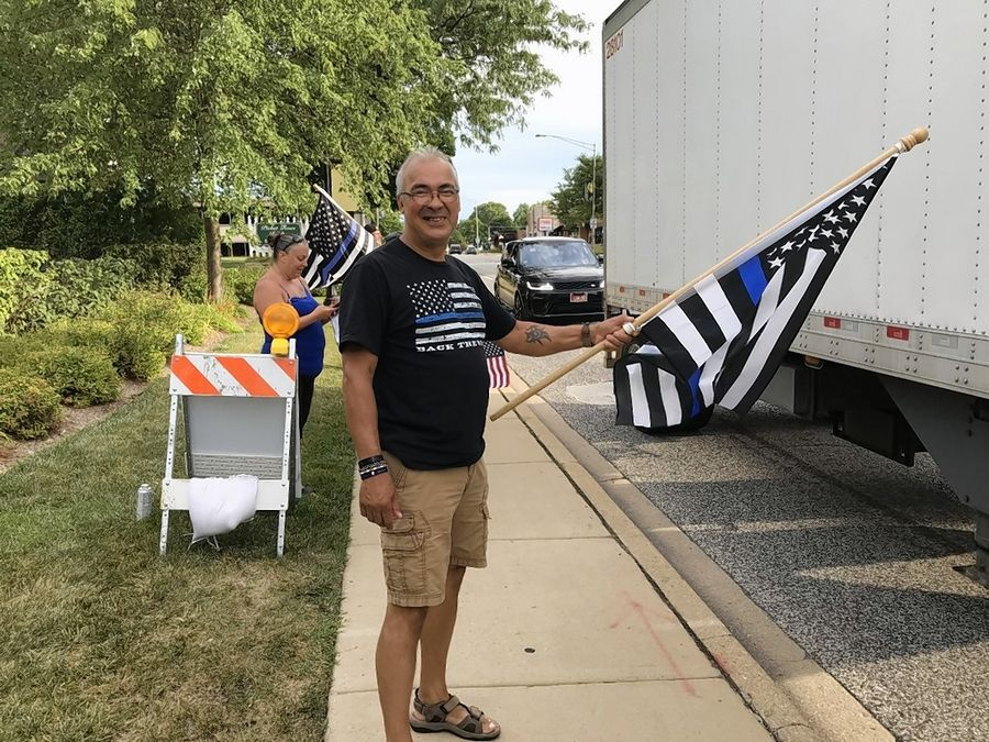 Des Plaines resident Pete Saverino carries a flag with a thin blue line in support of police Friday at a rally in Arlington Heights.