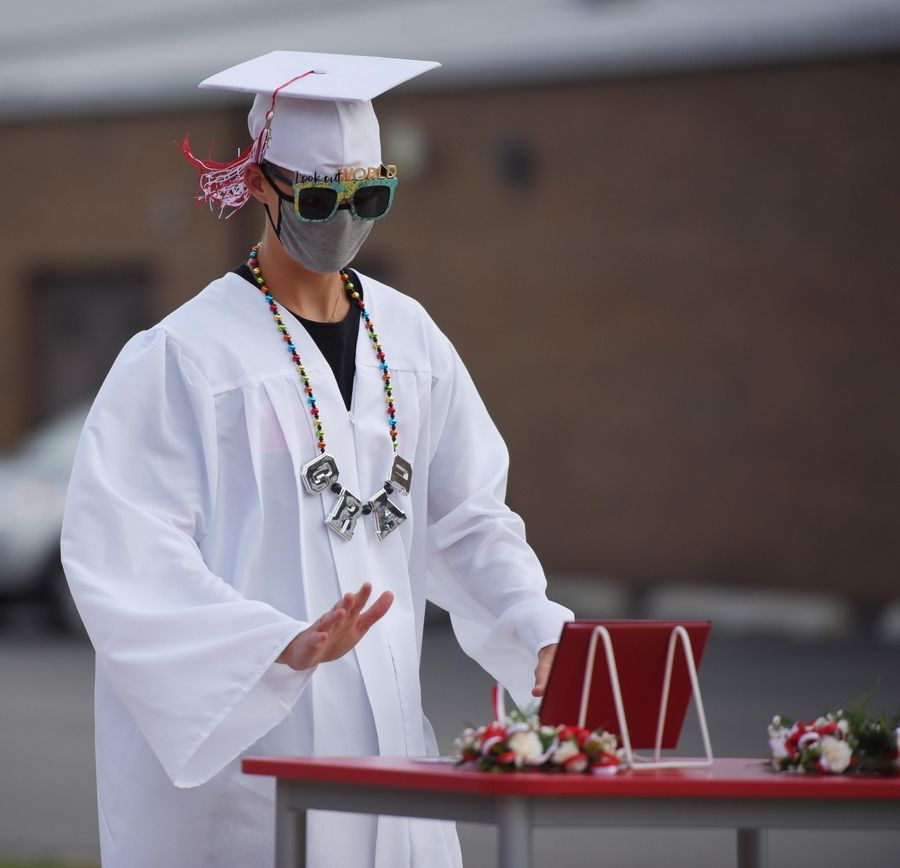 Timothy Christian High School graduate AJ Los reaches for his diploma at a drive up graduation ceremony at the school in Elmhurst Friday evening.