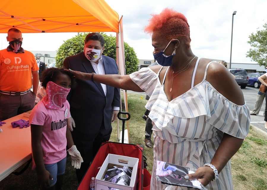 Gov. J.B. Pritzker and Olivia Tyler, 7, of Lombard, who came up with the idea to make masks to sell and raise money for a homeless shelter, hand out masks Friday to residents of the Red Roof Inn in Downers Grove.