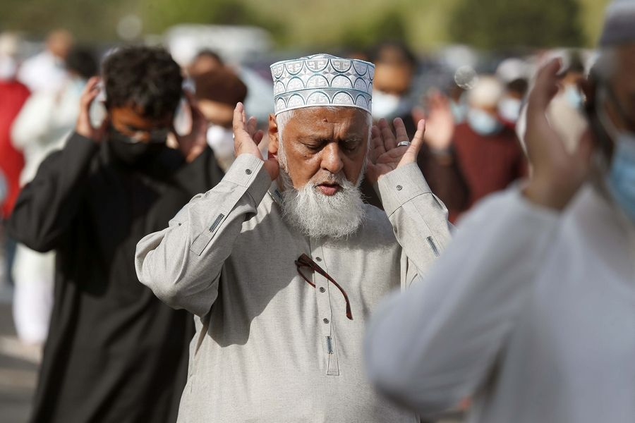 Ahmed Karim of Bartlett prays during one of two Eid al-Adha services Friday outside Schaumburg Boomers Stadium.