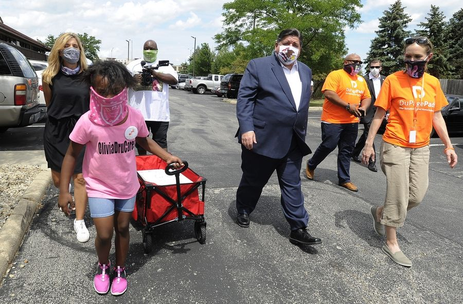 Gov. J.B. Pritzker met up with Olivia Tyler, 7, of Lombard, who came up with the idea to make masks to sell and raise money for a homeless shelter. They both handed out masks to the residents at the Red Roof Inn.