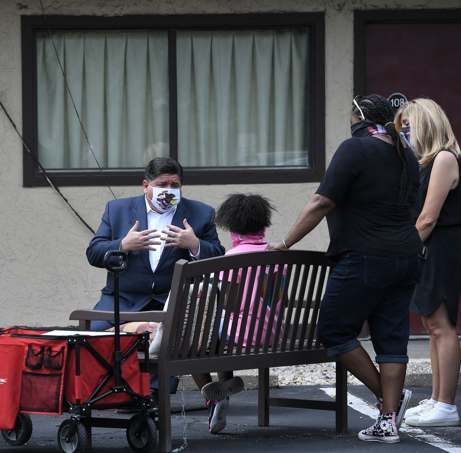 Gov. J.B. Pritzker sits down in the parking lot of Red Roof Inn in Downers Grove to talk with Olivia Tyler, 7, of Lombard, who came up with the idea to make masks to sell and raise money for a homeless shelter.