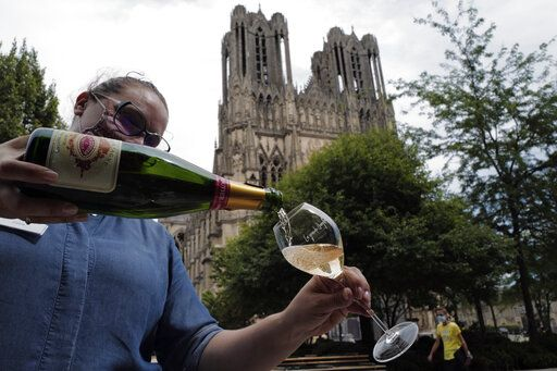 A waitress serves a glass of champagne at La Grande Georgette restaurant in front of the cathedral in Reims, the Champagne region, east of Paris, Tuesday, July 28, 2020. Producers in France's eastern Champagne region, headquarters of the global industry, say they've lost about 1.7 billion euros ($2 billion) in sales this year, as turnover fell by a third -  a hammering unmatched in living memory, and worse than the Great Depression.