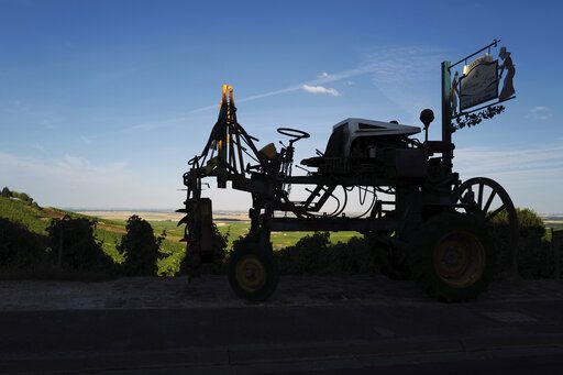 A piece of old agricultural machinery is displayed next to a vineyard in Avize, in the Champagne region, east of Paris, Tuesday, July 28, 2020. Producers in France's eastern Champagne region, headquarters of the global industry, say they've lost about 1.7 billion euros ($2 billion) in sales this year, as turnover fell by a third -  a hammering unmatched in living memory, and worse than the Great Depression.
