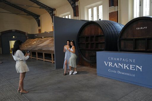 Visitors from London, take photos with a glass of Champagne as they visit the Vranken-Pommery Monopole in Reims, the Champagne region, east of Paris, Tuesday, July 28, 2020. Producers in France's eastern Champagne region, headquarters of the global industry, say they've lost about 1.7 billion euros ($2 billion) in sales this year, as turnover fell by a third -  a hammering unmatched in living memory, and worse than the Great Depression.
