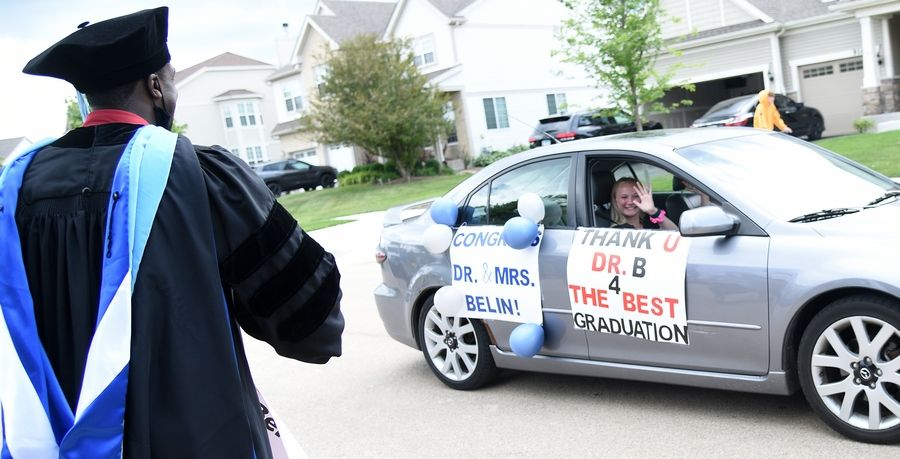A student wishes Huntley High School Principal Marcus Belin well during a surprise celebration in his honor at his Huntley home Friday after he received his doctoral degree from National Louis University.