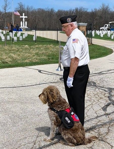 Navy veteran Jim Reynolds with Gander, an award-winning comfort dog, just before a service at Fort Sheridan Cemetery.