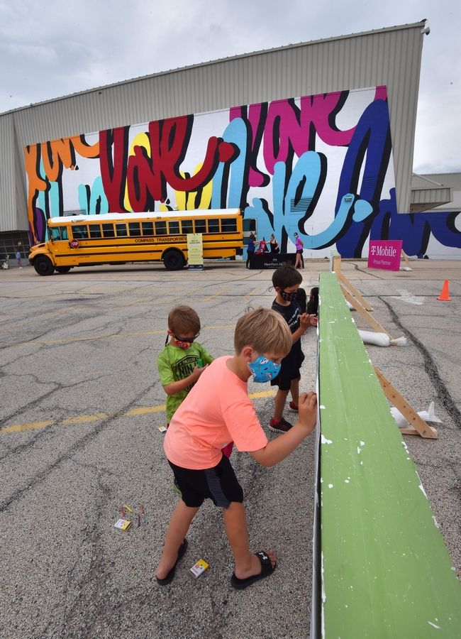 "David Marvin, 7, foreground, and brothers Evan, 10, and Zachary Miller, 7, use crayons to color in a mural at a ""Back-To-School Bash"" at Hawthorn Mall in Vernon Hills Saturday. All three boys are from Vernon Hills. The mall hosted the event as a way to collect school supplies in the school bus in the background."