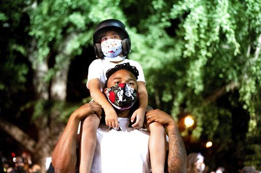 Leshan Terry hold his son Leshan Terry, Jr., 6, during a Black Lives Matter protest at the Mark O. Hatfield United States Courthouse on Friday, July 31, 2020, in Portland, Ore. Following an agreement between Democratic Gov. Kate Brown and the Trump administration to reduce federal officers in the city, nightly protests remained largely peaceful without major confrontations between demonstrators and officers.