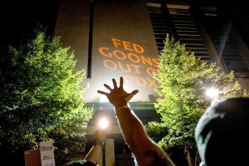 A Black Lives Matter protester raises his hand as text is projected onto the Mark O. Hatfield United States Courthouse on Friday, July. 31, 2020, in Portland, Ore. Following an agreement between Democratic Gov. Kate Brown and the Trump administration to reduce federal officers in the city, the protest remained largely peaceful without major confrontations between demonstrators and officers.