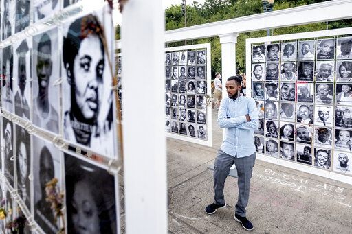 Adbi Noor examines a memorial for black lives lost to violence on Friday, July 31, 2020, in Portland, Ore. Following an agreement between Democratic Gov. Kate Brown and the Trump administration to reduce federal officers in the city, nightly protests remained largely peaceful without major confrontations between demonstrators and officers.