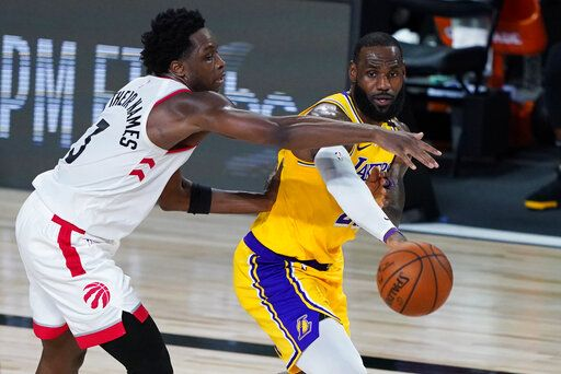 Los Angeles Lakers' LeBron James passes around Toronto Raptors' OG Anunoby (3) during the second half of an NBA basketball game Saturday, Aug. 1, 2020, in Lake Buena Vista, Fla.