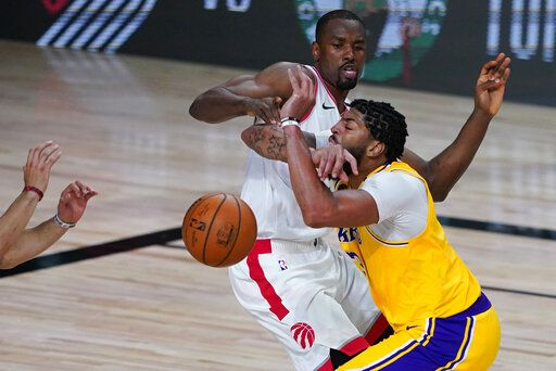 Los Angeles Lakers' Anthony Davis, right, drives into Toronto Raptors' Serge Ibaka (9) during the second half of an NBA basketball game Saturday, Aug. 1, 2020, in Lake Buena Vista, Fla.