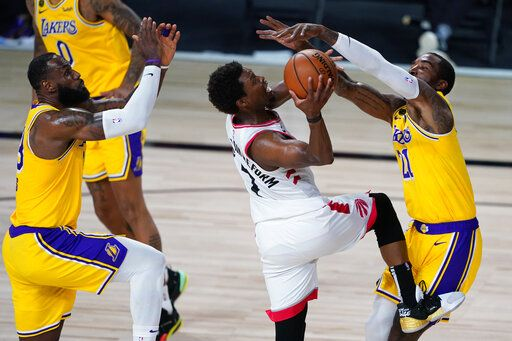 Los Angeles Lakers' LeBron James, left, and JR Smith, right, guard Toronto Raptors' Kyle Lowry during the second half of an NBA basketball game Saturday, Aug. 1, 2020, in Lake Buena Vista, Fla.