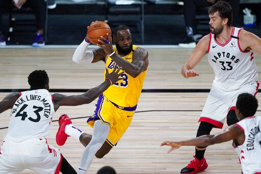 Los Angeles Lakers' LeBron James (23) drives around Toronto Raptors' Pascal Siakam (43) and Marc Gasol (33) during the first half of an NBA basketball game Saturday, Aug. 1, 2020, in Lake Buena Vista, Fla.