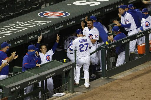 Chicago Cubs' Jason Kipnis (27) is congratulated by teammates after hitting a solo home run against the Pittsburgh Pirates during the fourth inning of a baseball game in Chicago, Friday, July 31, 2020.