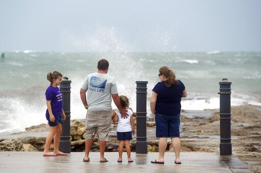 Elizabeth Whittemore (from left), along with her father James, sister Jordan and mother Susan, stand at the end of the South Jetty in Fort Pierce on Sunday, Aug. 2, 2020, watch the waves crash over the rocks brought by the high winds of Tropical Storm Isaias churning off the coast. (Patrick Dove/TCPalm.com via AP)