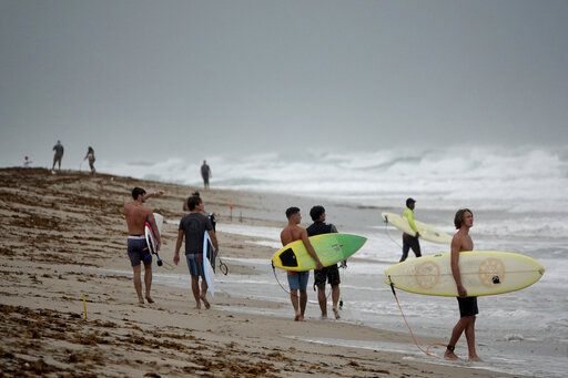 Surfers in Delray Beach enjoy the waves, Sunday, Aug. 2, 2020, as Tropical Storm Isaias brushes past the East Coast of Florida. (Joe Cavaretta/South Florida Sun-Sentinel via AP)