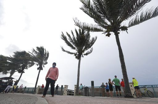 People gather to watch the strong waves on the beach as palm trees sway in the wind, Sunday, Aug. 2, 2020, in Vero Beach, Fla. Isaias weakened from a hurricane to a tropical storm late Saturday afternoon, but was still expected to bring heavy rain and flooding as it barrels toward Florida.