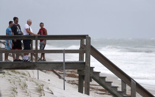Beach goers watch waves churned up by Tropical Storm Isaias near Jaycee Beach Park, Sunday, Aug. 2, 2020, in Vero Beach, Fla. Isaias weakened from a hurricane to a tropical storm late Saturday afternoon, but was still expected to bring heavy rain and flooding as it barrels toward Florida.