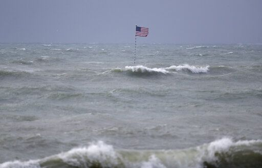 An American flag flies from the shipwreck of the Breconshire, as waves churned up by Tropical Storm Isaias crash around it, Sunday, Aug. 2, 2020, in Vero Beach, Fla. Isaias weakened from a hurricane to a tropical storm late Saturday afternoon, but was still expected to bring heavy rain and flooding as it barrels toward Florida. The Breconshire was a cargo ship that ran aground in 1894.