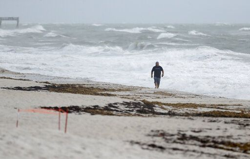 A beach goer walks along the shore as waves churned up by Tropical Storm Isaias crash near Jaycee Beach Park, Sunday, Aug. 2, 2020, in Vero Beach, Fla. Isaias weakened from a hurricane to a tropical storm late Saturday afternoon, but was still expected to bring heavy rain and flooding as it barrels toward Florida.