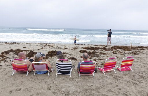 Spectators watch surfers in Delray Beach, Sunday, Aug. 2, 2020, as Tropical Storm Isaias brushes past the East Coast of Florida. (Joe Cavaretta/South Florida Sun-Sentinel via AP)