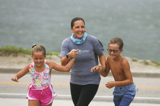 Jennifer Wiggins, center, points to large waves as she walks toward the beach with her children Abigail, left, 7, and Owen, 9, at House of Refuge as Tropical Storm Isaias winds pick up Sunday, Aug. 2, 2020, in Stuart, Fla. (Crystal Vander Weit/TCPalm.com via AP)