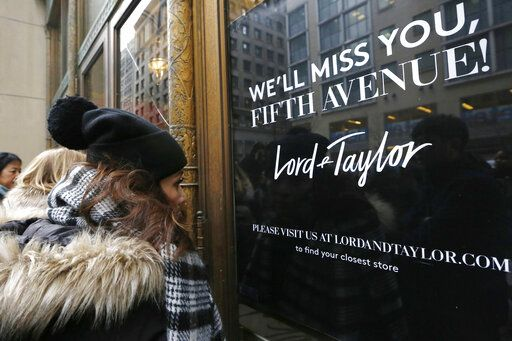 FILE - In this Jan. 2, 2019, file photo, women peer in the front door of Lord & Taylor's flagship Fifth Avenue store which closed for good in New York. New York landmark retailer Lord & Taylor has filed for bankruptcy, joining a growing list of retailers flummoxed by the pandemic.