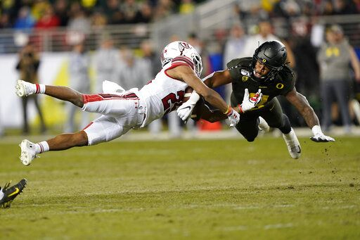 FILE - In this Dec. 6, 2018, file photo, Oregon safety Jevon Holland (8) breaks up a pass for Utah wide receiver Jaylen Dixon (25) during the first half of the Pac-12 Conference championship NCAA college football game in Santa Clara, Calif. A group of Pac-12 football players on Sunday, Aug. 2, 2020, threatened to opt out of the coming season unless its concerns about competing during the COVID-19 pandemic and other racial and economic issues in college sports are addressed.