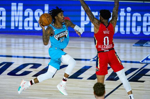 Memphis Grizzlies' Ja Morant (12) misses a shot at the buzzer over New Orleans Pelicans' Nickeil Alexander-Walker (0) during the first half of an NBA basketball game Monday, Aug. 3, 2020 in Lake Buena Vista, Fla.