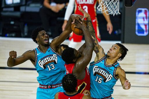 New Orleans Pelicans' Zion Williamson (1) has his shot blocked by Memphis Grizzlies' Brandon Clarke (15) and Jaren Jackson Jr. (13) during the second half of an NBA basketball game Monday, Aug. 3, 2020 in Lake Buena Vista, Fla.