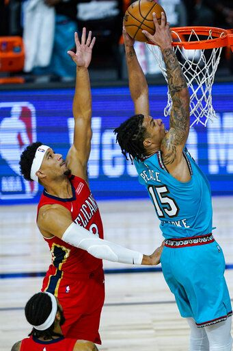 Memphis Grizzlies' Brandon Clarke (15) gets a dunk in front of New Orleans Pelicans' Josh Hart (3) during the first half of an NBA basketball game Monday, Aug. 3, 2020 in Lake Buena Vista, Fla.