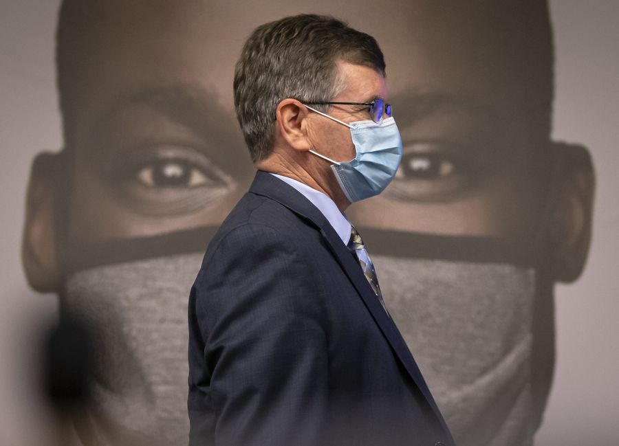 "Springfield Mayor Jim Langfelder walks past one of the images used by Gov. J.B. Pritzker to unveil a new mask awareness campaign called ""It Only Works If You Wear It"" on Monday."
