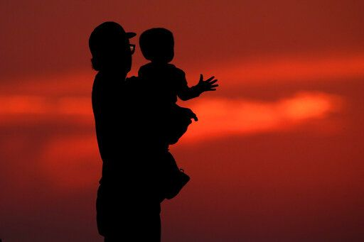 FILE - In this June 26, 2020 file photo, a man and his son are silhouetted against the sky as they watch the sunset from a park in Kansas City, Mo. Health experts once thought 2020 might be the worst year yet for a rare paralyzing disease that has been hitting U.S. children for the past decade.  But they now say the coronavirus pandemic could disrupt the pattern for the mysterious illnesses, which spike every other year starting in late summer.